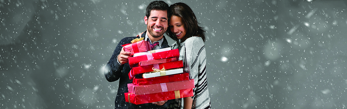 A couple celebrating Christmas with gifts.
